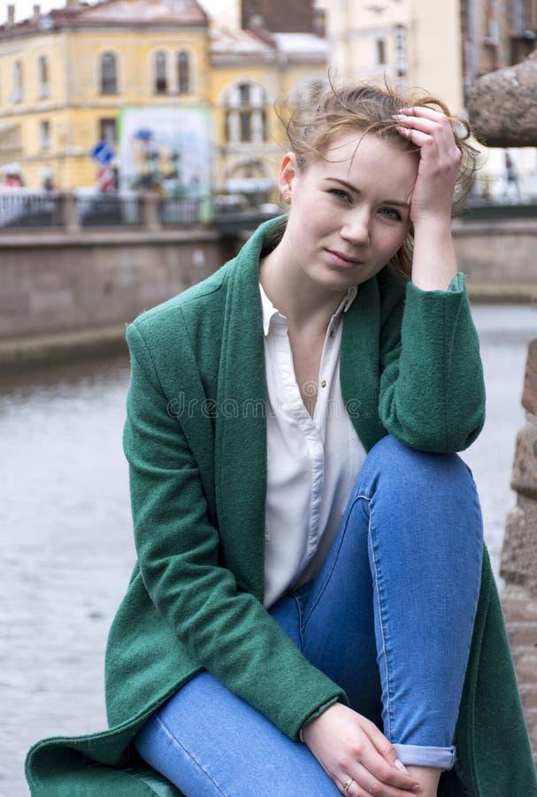 1 ein Mädchen in der weißen Bluse und im grünen Mantel im Hintergrund von t lizenzfreie stockfotos