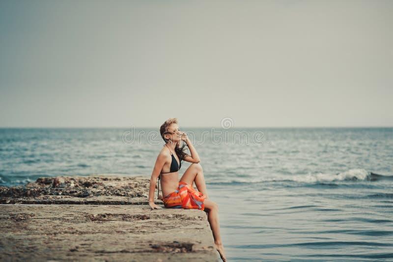 Ein Mädchen in einem Badeanzug auf einem Pier stockfotos