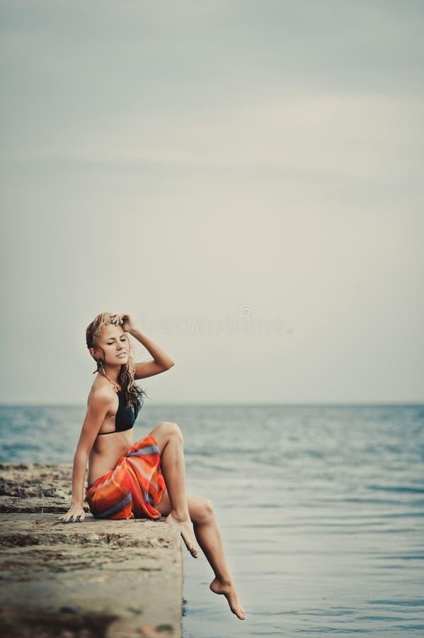 Ein Mädchen in einem Badeanzug auf einem Pier stockfotografie