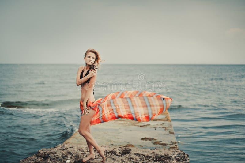 Ein Mädchen in einem Badeanzug auf einem Pier stockbild