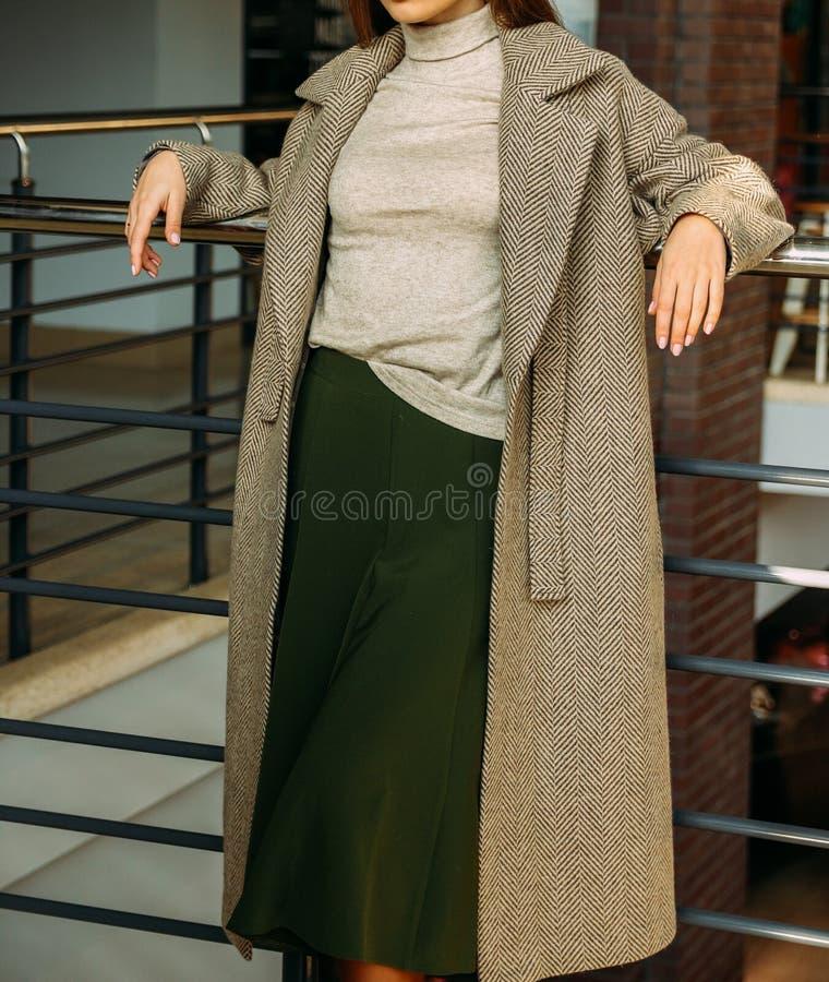 Ein Mädchen in einem beige Mantel und in einer Strickjacke, ein Grün, langer Rock, Stände nahe dem Geländer, lehnend auf einem Me stockbild