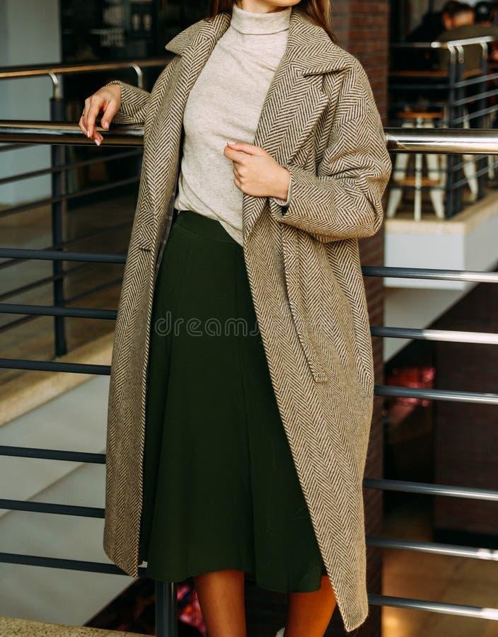 Ein Mädchen in einem beige Mantel und in einer Strickjacke, ein Grün, langer Rock, Stände nahe dem Geländer, lehnend auf einem Me lizenzfreies stockbild