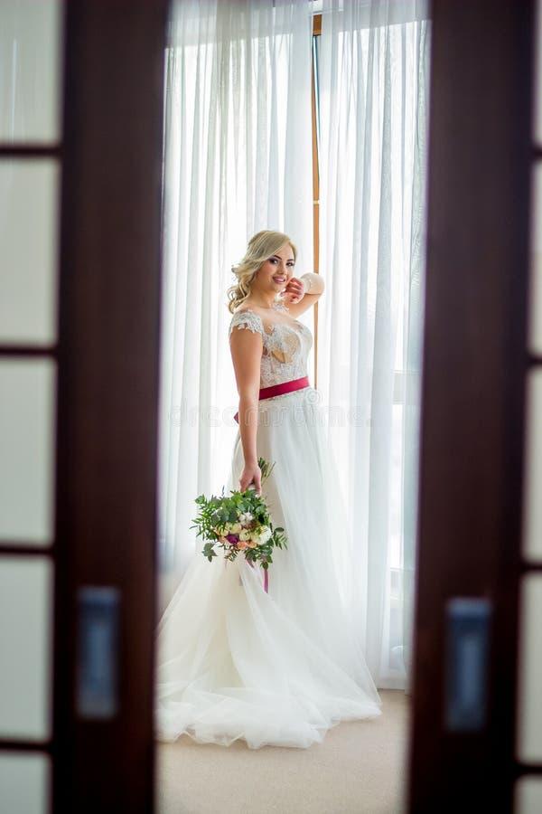 Ein Mädchen in einem Heiratskleid mit Make-up und dem Haar steht in einem hellen Hotelzimmer nahe dem Fenster in einem Heiratskle lizenzfreie stockfotos