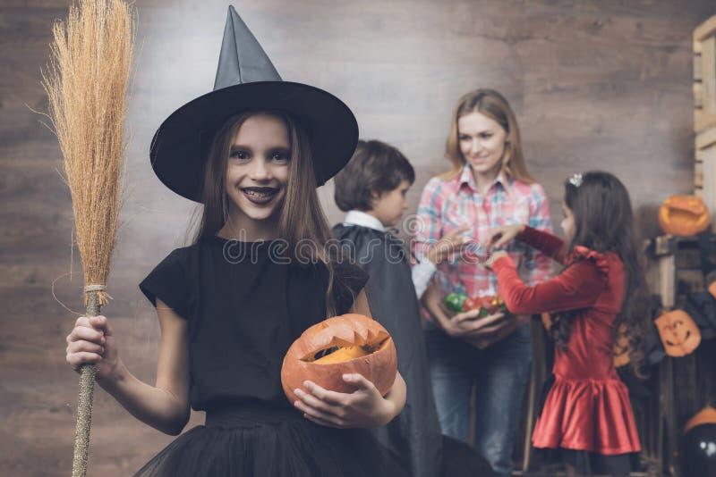 Ein Mädchen in einem Hexenkostüm steht auf dem Hintergrund anderer Kinder und der Frau Mädchen, das einen Besen und einen Kürbis  stockfotos
