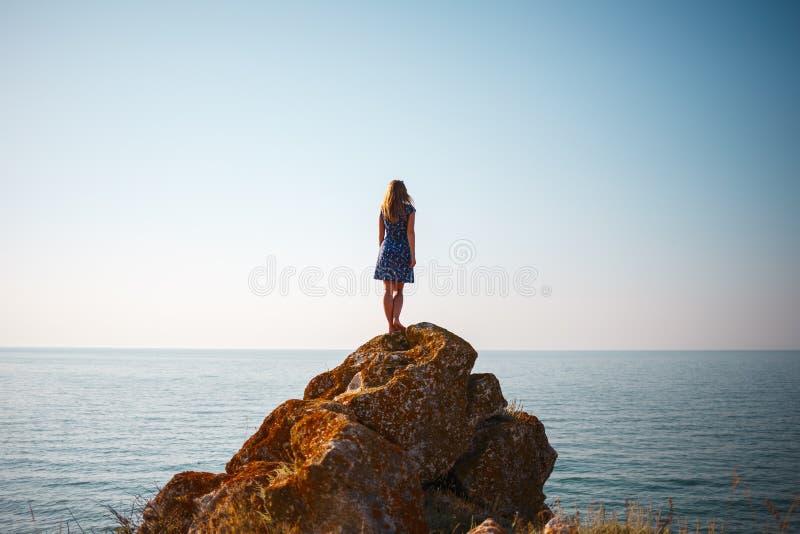 Ein Mädchen in einem Kleid steht auf einem Stein und Blicken in dem blauen Meer lizenzfreies stockfoto