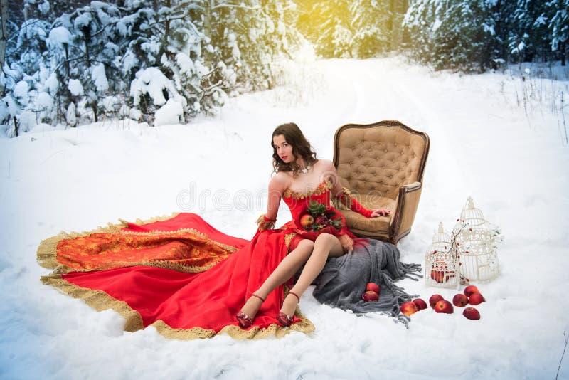 Ein Mädchen in einem Märchenbild einer Königin wirft in einem schneebedeckten Winterwald auf stockfotos