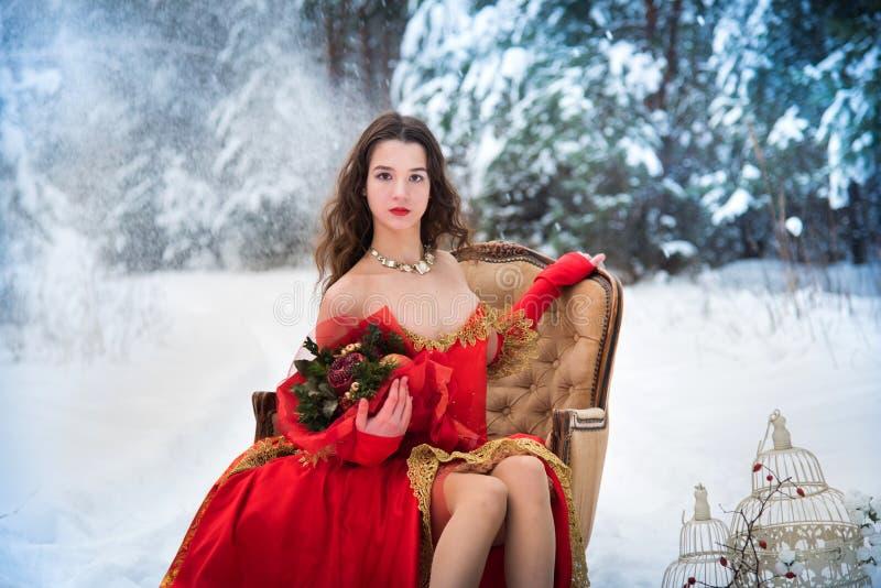 Ein Mädchen in einem Märchenbild einer Königin wirft in einem schneebedeckten Winterwaldlang roten Kleid, Blumenstrauß von Frücht stockfotografie