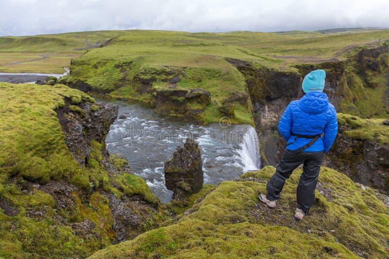 Ein Mädchen in einem Matrosen steht am Rand einer Klippe durch den Fagrifoss-Wasserfall lizenzfreies stockbild