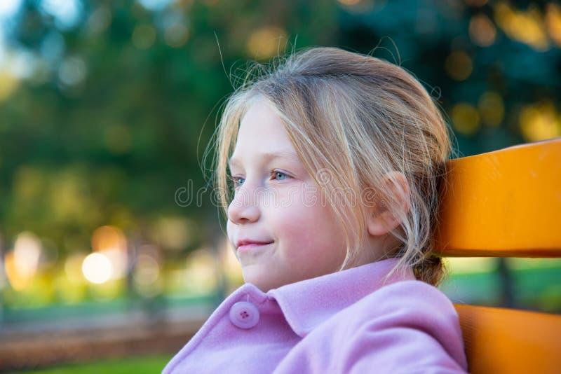 Ein Mädchen in einem rosa Mantel sitzt auf einer gelben Bank im Park, ein Nahaufnahmekinderbild stockbilder