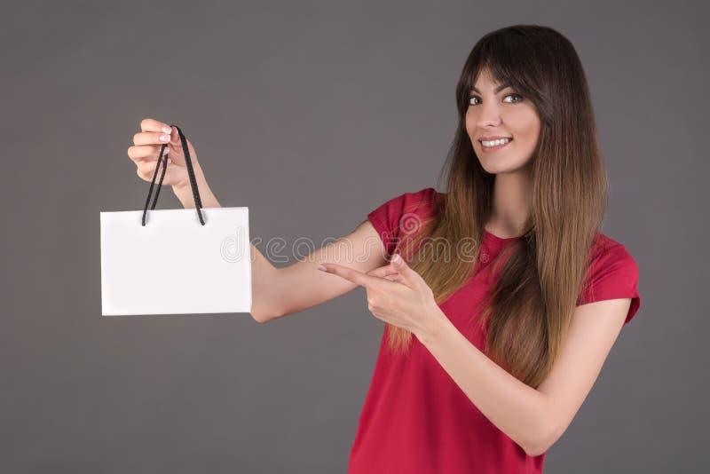 Ein Mädchen in einem roten T-Shirt mit einer weißen Geschenktasche Frauenkaufangebote ein Produkt lizenzfreies stockbild