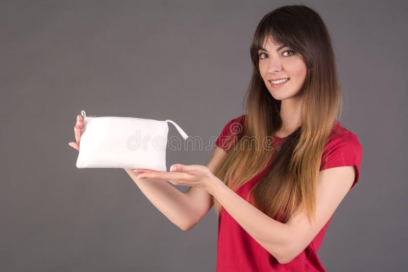 Ein Mädchen in einem roten T-Shirt mit einer weißen Kosmetiktasche stockbilder