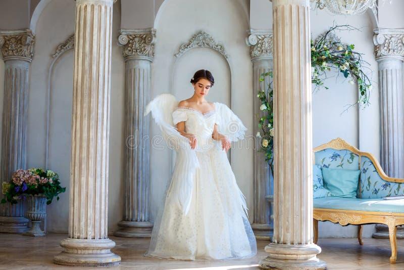 Ein Mädchen in einem schönen Kleid und in weißen Flügeln eines Engels spornt an lizenzfreies stockfoto