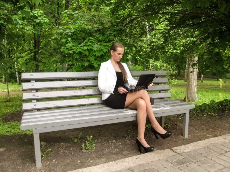 Ein Mädchen in einem schwarzen Kleid, in einer weißen Jacke und in Schuhen mit Fersen öffnet einen Laptop, der auf einer Bank im  stockbilder