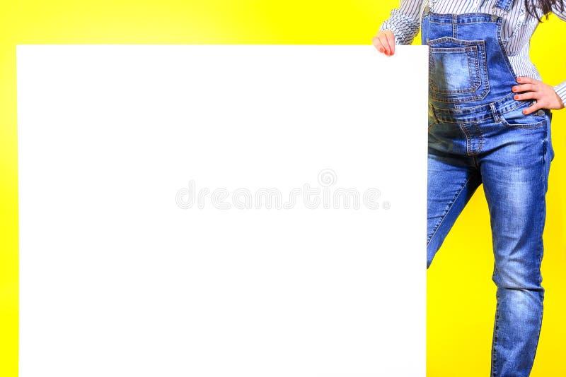 Ein Mädchen in einem Smoking auf einem gelben Studiohintergrund hält ein großes weißes Blatt lizenzfreie stockfotos