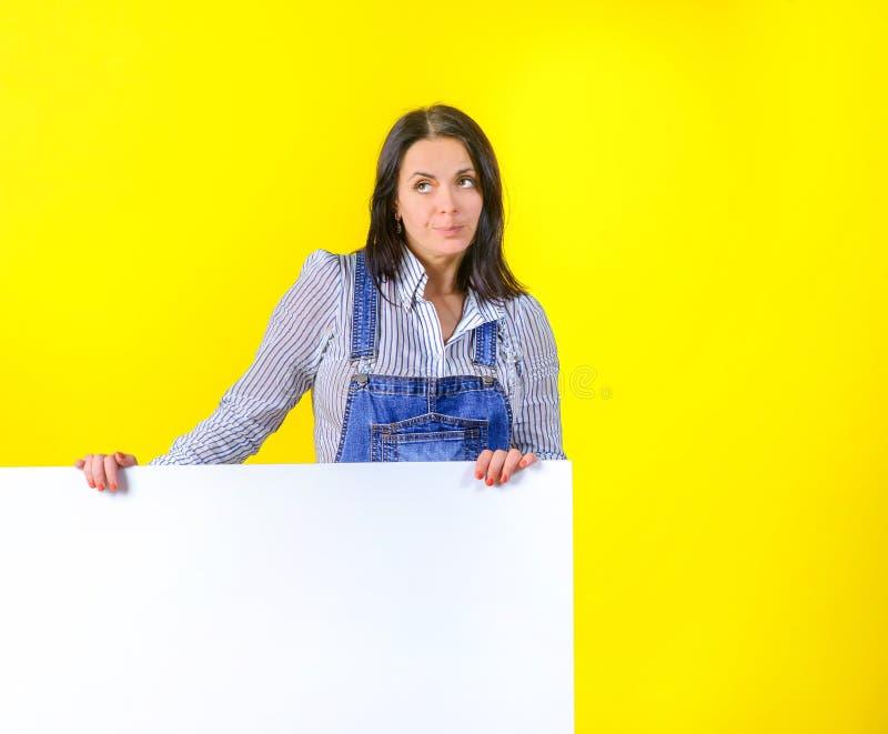 Ein Mädchen in einem Smoking auf einem gelben Studiohintergrund hält ein großes weißes Blatt, einen Platz für eine Aufschrift stockbilder