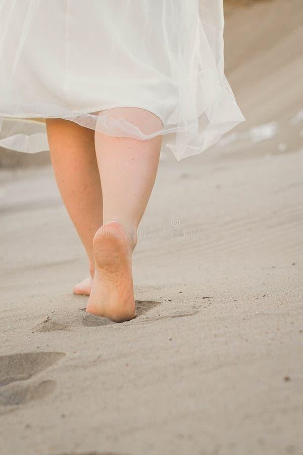 Ein Mädchen in einem weißen Kleid gehend in den Sand lizenzfreie stockfotografie