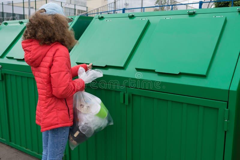 Ein Mädchen in einer roten Jacke kam, um eine Tüte Müll in einen Mülltank zu werfen stockbild