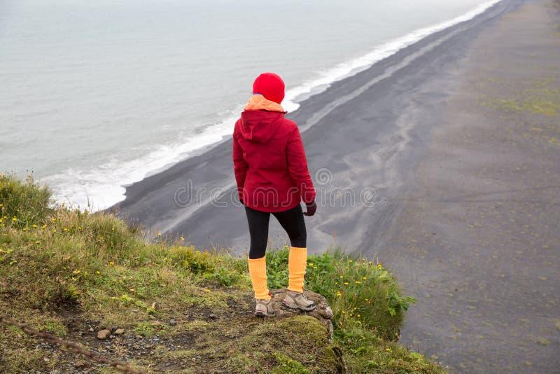 Ein Mädchen in einer roten Jacke steht auf einer Klippe über dem Seeufer stockfotografie