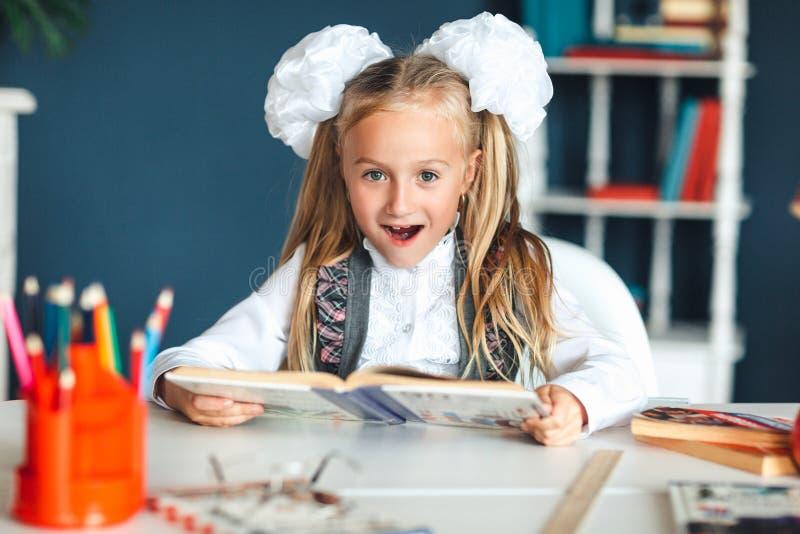 Ein Mädchen in einer Schuluniform betrachtet ein Lehrbuch mit einem überraschten Gesicht Mädchen, das versucht, Haben zu vieler H stockfotografie