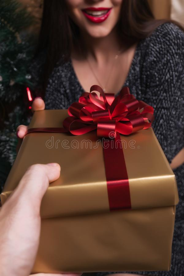 Ein Mädchen empfängt ein Geschenk von einem Kerl nahe dem Weihnachtsbaum lizenzfreie stockbilder