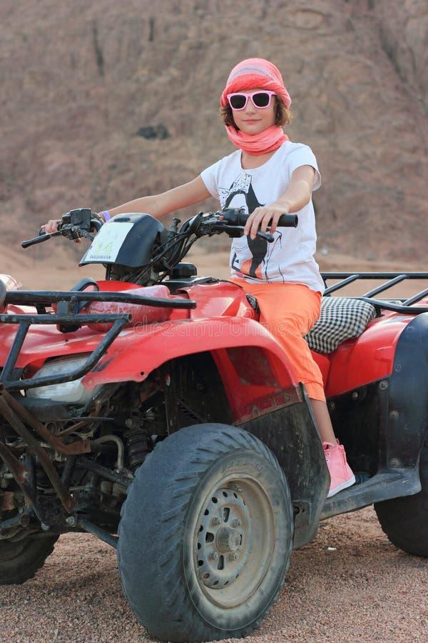 Ein Mädchen fährt in die Wüste auf eine elektrische Maschine lizenzfreies stockbild