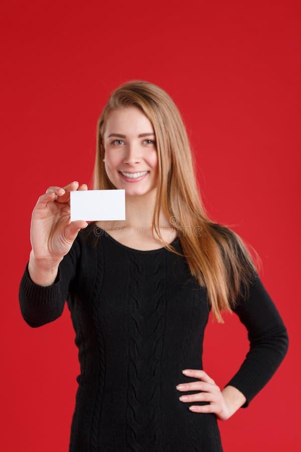 Ein Mädchen hält eine Visitenkarte und ein Lächeln lizenzfreie stockbilder
