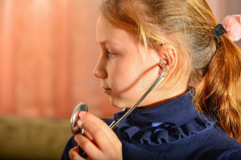 Ein Mädchen hält ein Stethoskop in seinen Händen und hört auf den Patienten, Heimspiel am Doktor lizenzfreie stockfotografie