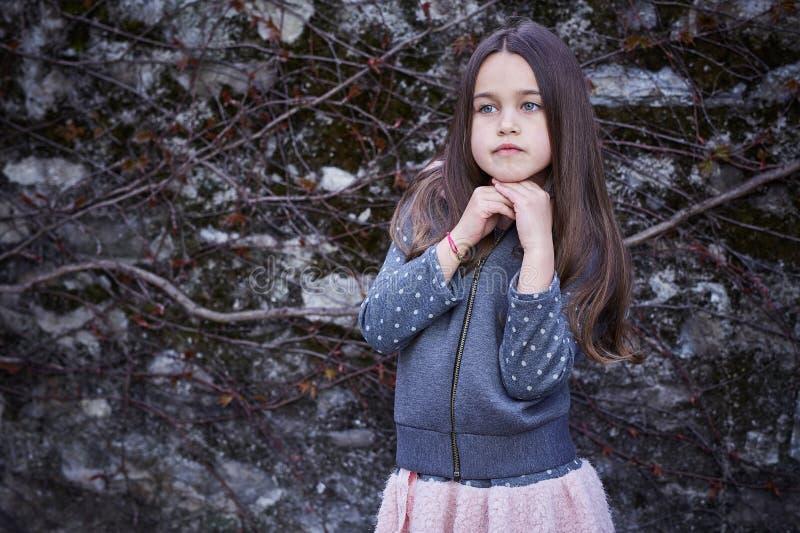 Ein Mädchen im rosa Rock und in der grauen Jacke lizenzfreie stockfotografie