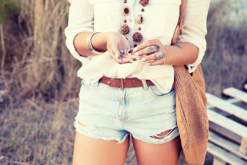 Ein Mädchen im Stil einer Hippie in den Verzierungen, das bochos Chic hält ein Oberteil von Schnecken in ihren Händen Weinlesefar lizenzfreie stockfotografie