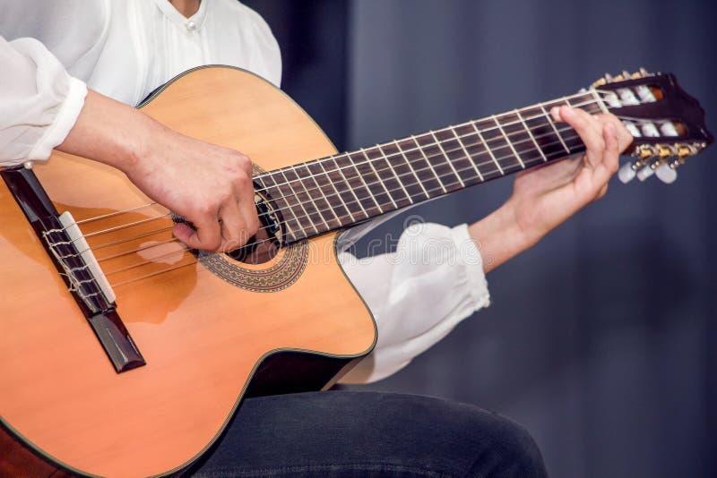 Ein Mädchen im weißen Hemd, das Gitarre spielt Leistung am Konzert des guitarist_ lizenzfreie stockbilder