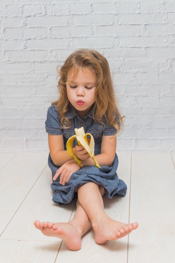Ein Mädchen, ein Kind, zum der köstlichen gesunden Banane gegen einen Ziegelstein zu essen stockfotografie