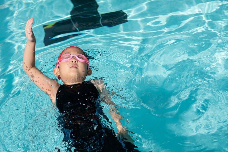 Ein Mädchen lernen, wie man im Schwimmkurs schwimmt stockfotografie