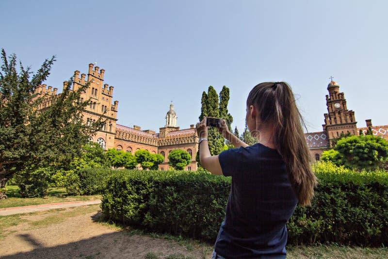 Ein Mädchen macht ein Foto an einem Handy eines historischen Gebäudes lizenzfreies stockbild