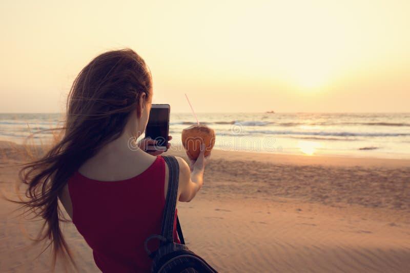 Ein Mädchen macht Fotos einer Kokosnuss lizenzfreies stockbild