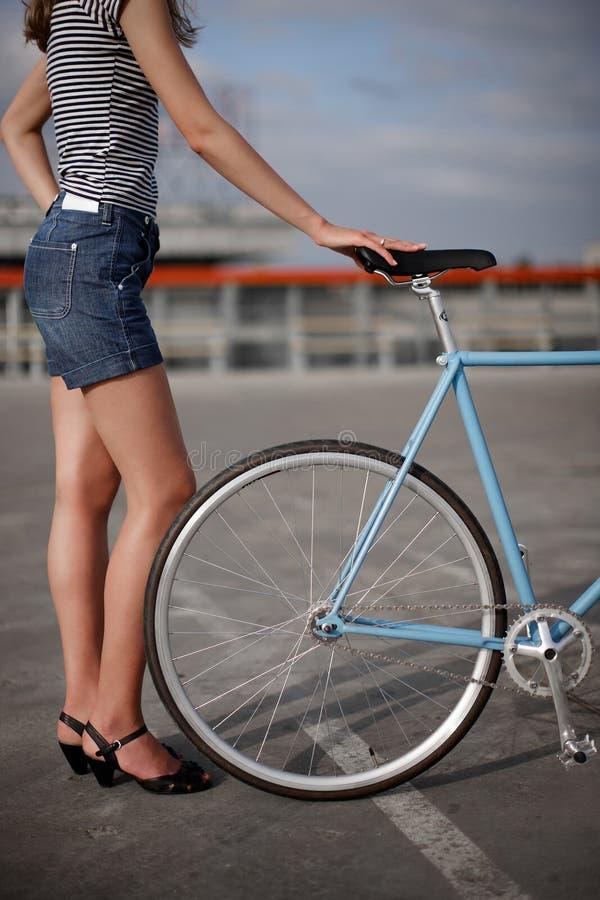 Ein Mädchen mit blauem Fahrrad lizenzfreie stockfotografie