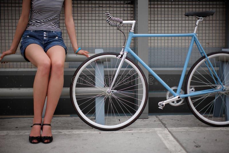 Ein Mädchen mit blauem Fahrrad lizenzfreie stockbilder