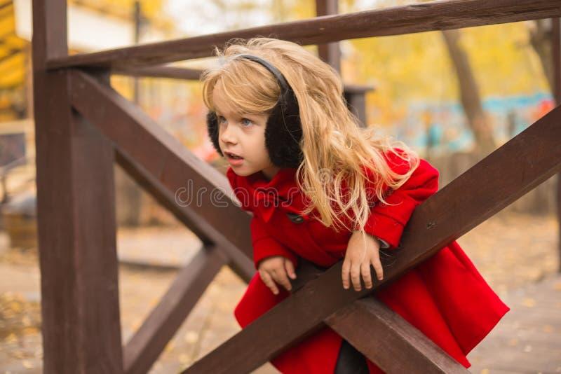 Ein Mädchen mit dem blonden Haar spielt am Bretterzaun stockfoto
