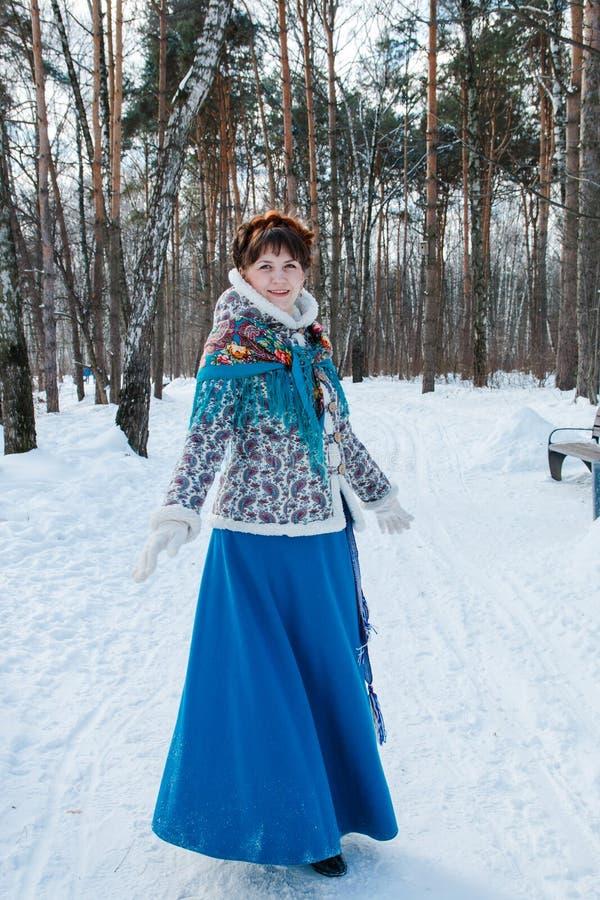 Ein Mädchen mit dem schönen Haar auf ihrem Kopf in einer slawischen Art im vollen Wachstum im Winterwald lizenzfreies stockfoto