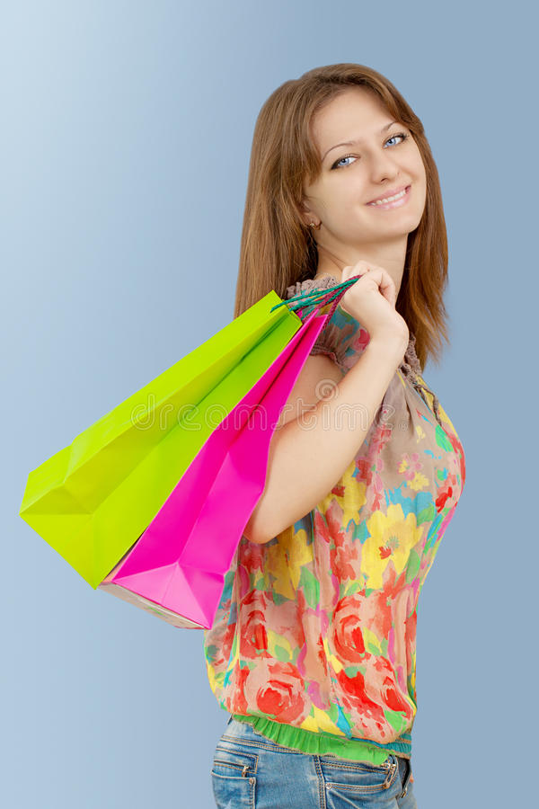 Ein Mädchen mit den Papiertüten, die Kamera und das Lächeln betrachten lizenzfreie stockfotos