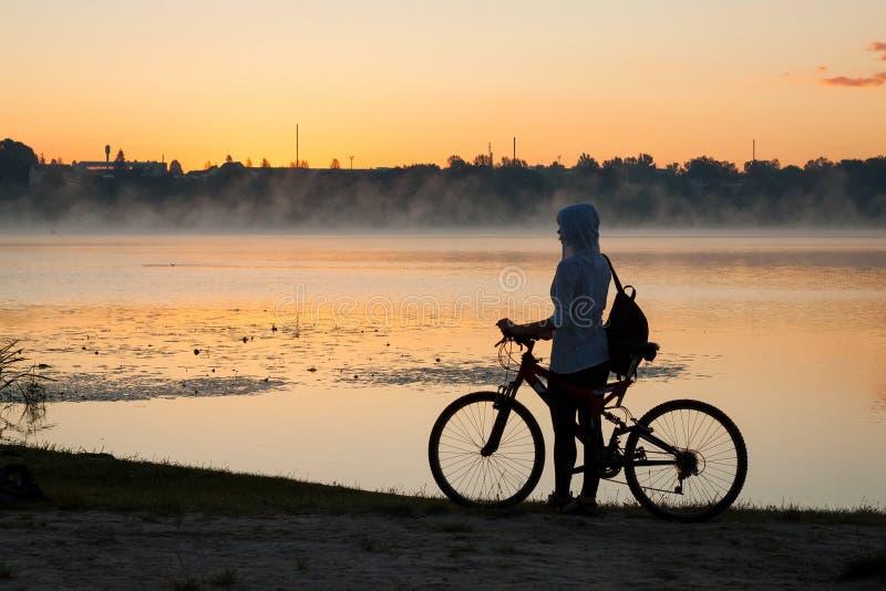 Ein Mädchen mit einem Fahrrad nahe dem See am Sommermorgen lizenzfreies stockfoto