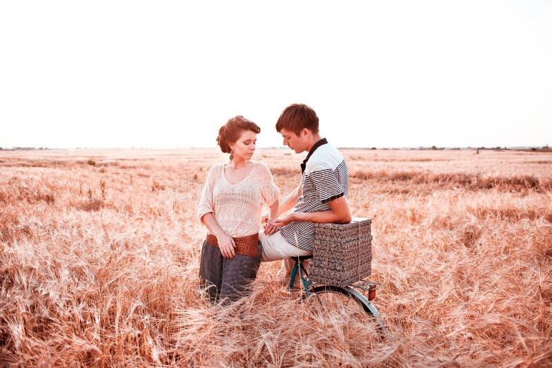 Ein Mädchen mit einem Kerl, der entlang ein Roggenfeld mit einem Fahrrad geht und einander betrachtet lizenzfreie stockfotos