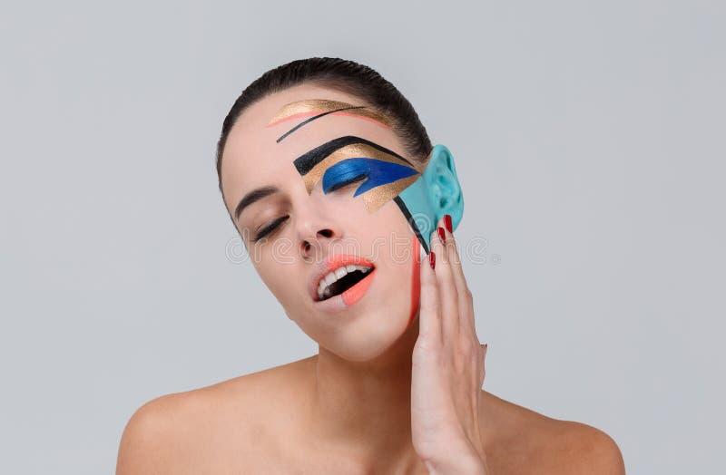 Ein Mädchen mit einem kreativen geometrischen Make-up, das geschlossen wird, mustert wenig mit dem offenen Mund und gestoßenem Ko stockbilder