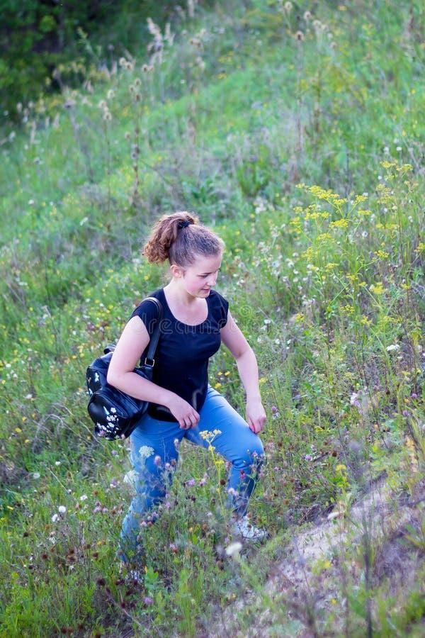 Ein Mädchen mit einem Rucksack geht den Hügel hinauf Aktiver Rest auf Natur stockbilder