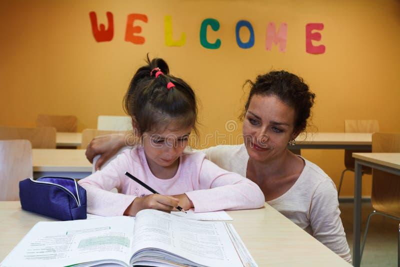Ein Mädchen mit ihrem Lehrer bereiten Lektionen vor stockfotos
