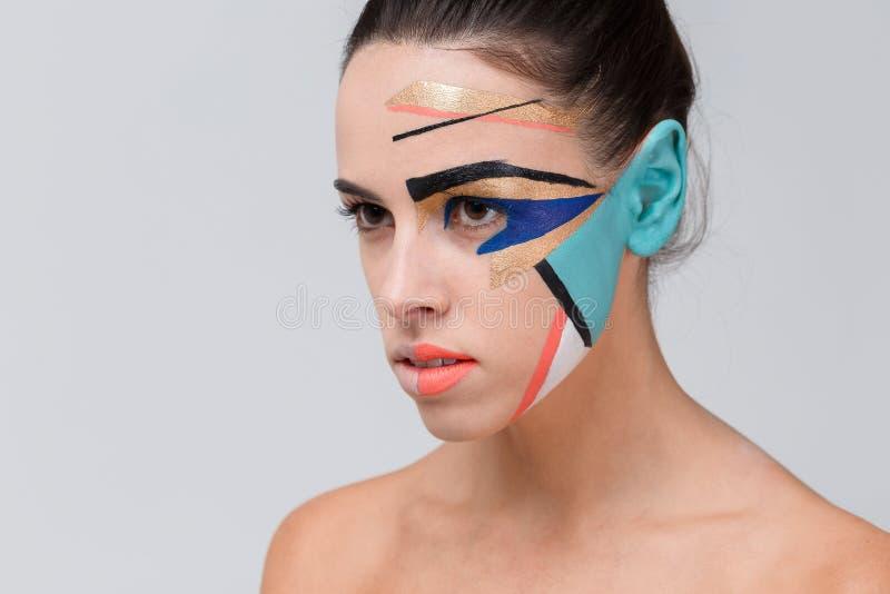 Ein Mädchen, mit kreativem geometrischem Make-up auf ihrem Gesicht lizenzfreie stockbilder