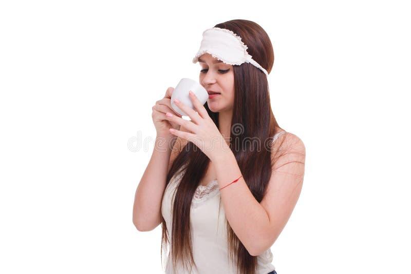 Ein Mädchen mit Maske für das Schlafen auf Kopf, trinkt etwas von einer Schale Lokalisiert auf Weiß stockfotografie