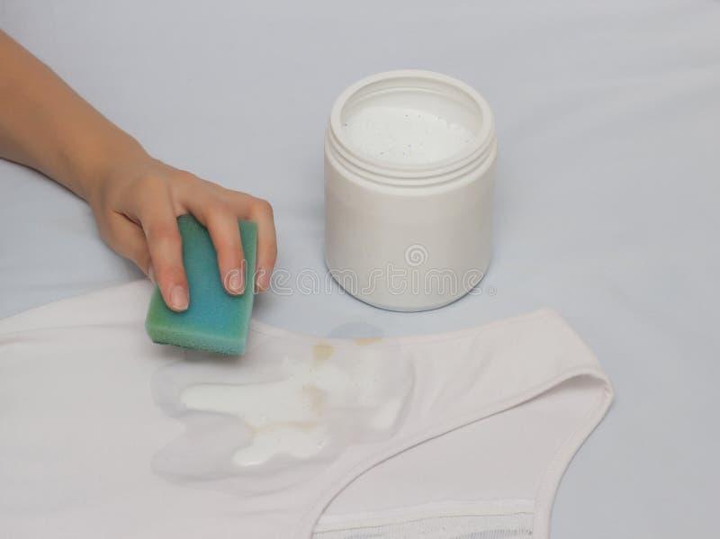 Ein Mädchen säubert einen Fleck mit einem Schwamm auf einem T-Shirt unter Verwendung eines Fleckenentferners, Nahaufnahme, Hand lizenzfreie stockfotos