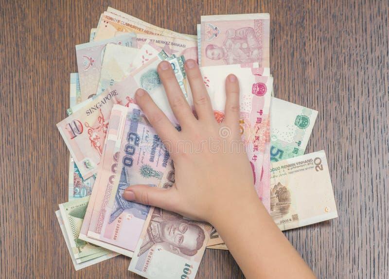 Ein Mädchen ` s Handpressen ein Bündel unterschiedliches asiatisches Geld zum Holztisch stockbild