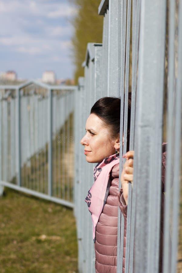 Ein Mädchen schaut durch die Barren eines Metallzaunes In einer Federjacke verkleidet, um den Nacken stockfotos