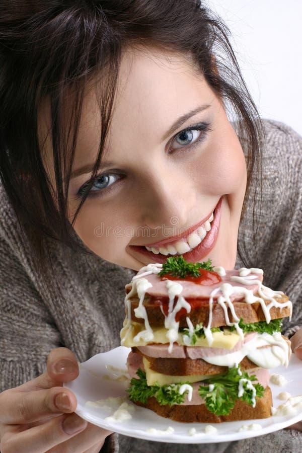 Ein Mädchen schlägt ein Sandwich vor stockfotos